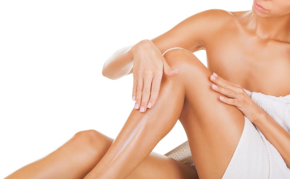 Donna che accarezza le proprie gambe finalmente lisce e libere dalla follicolite grazie all'epilazione permanente