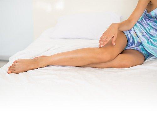 Donna che accarezza le proprie gambe lisce, libera dall'incubo dei peli superflui