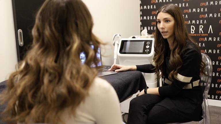 Cliente donna di spalle ed estetista seduta di fronte a lei che parla durante una consulenza di epilazione permanente